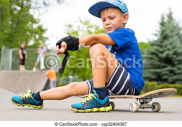 Boy on Skateboard Adjusting Elbow Pad in Park - csp32404367
