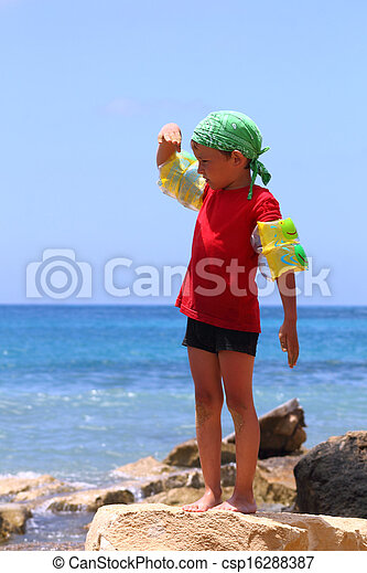 boy on the beach looking into the distance - csp16288387