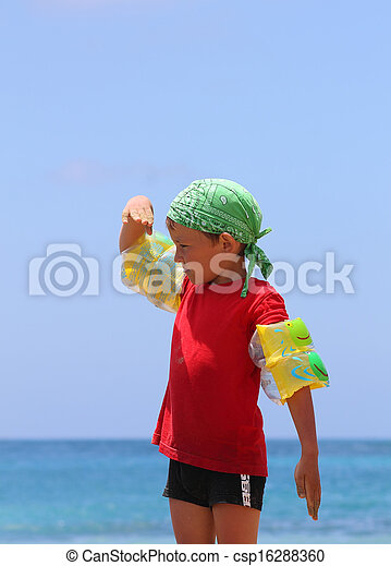boy on the beach looking into the distance - csp16288360