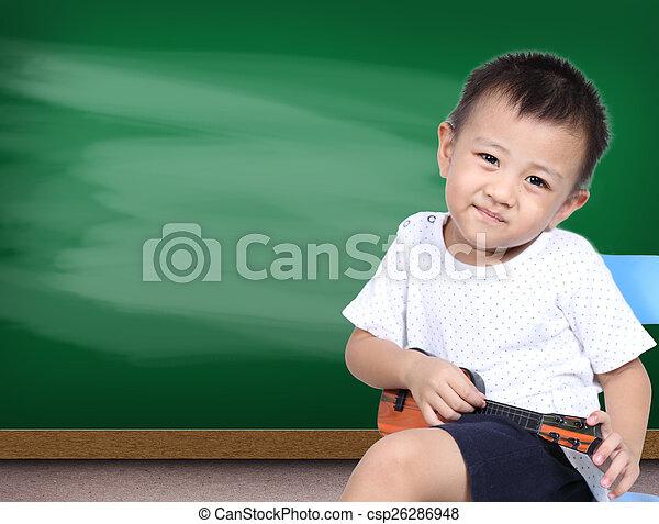 Boy playin ukulele guitar with green chalk board background - csp26286948