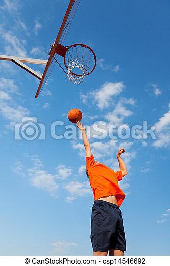 Boy Playing Basketball Against Blue Sky - csp14546692