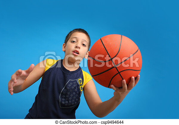Boy playing basketball. Blue background - csp9494644