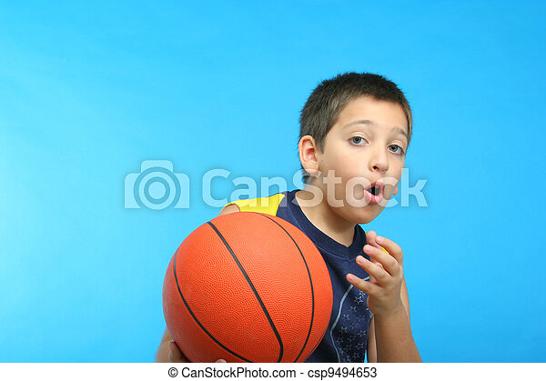 Boy playing basketball. Blue background - csp9494653