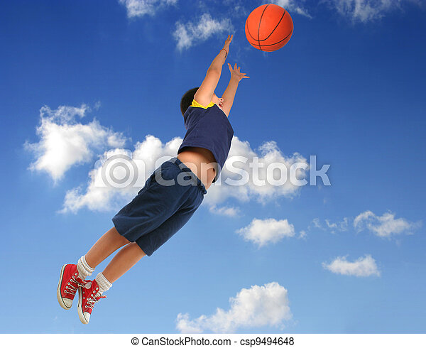 Boy playing basketball. Flying with blue sky - csp9494648
