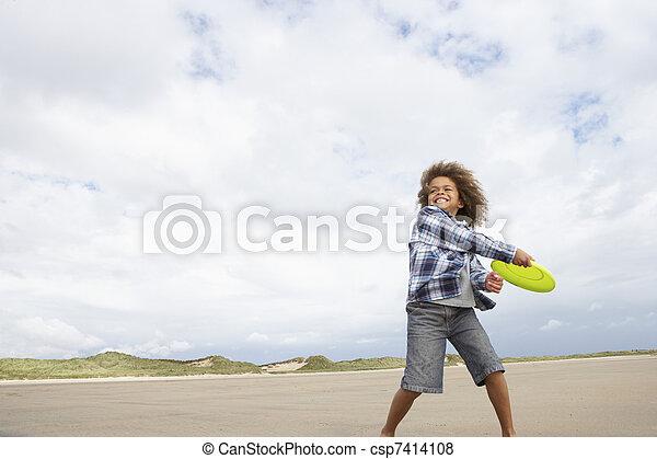 Boy playing frisbee on beach - csp7414108