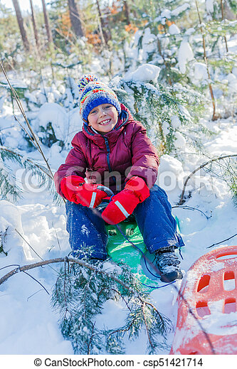 Boy playing with sled in big snow in winter. Happy caucasian child playing in snow forest