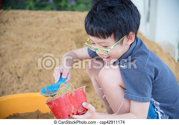 boy playing sand in sandbox - csp42911174