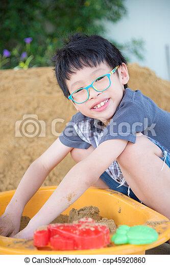 boy playing sand in sandbox - csp45920860