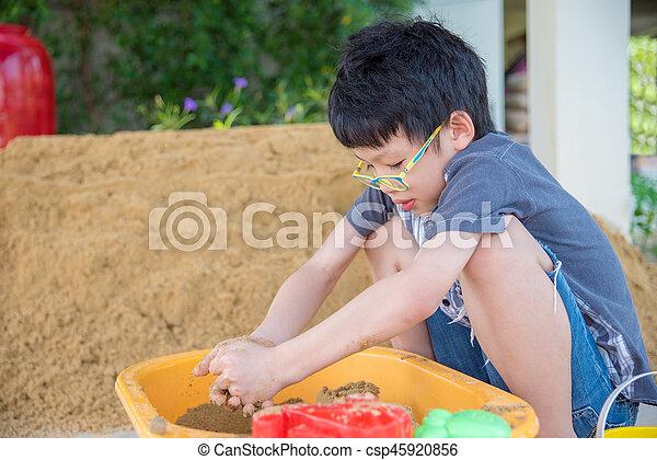 boy playing sand in sandbox - csp45920856