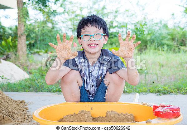 boy playing sand in sandbox - csp50626942