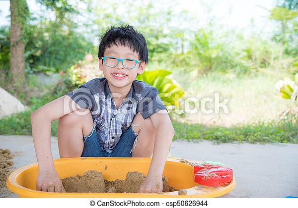 boy playing sand in sandbox - csp50626944