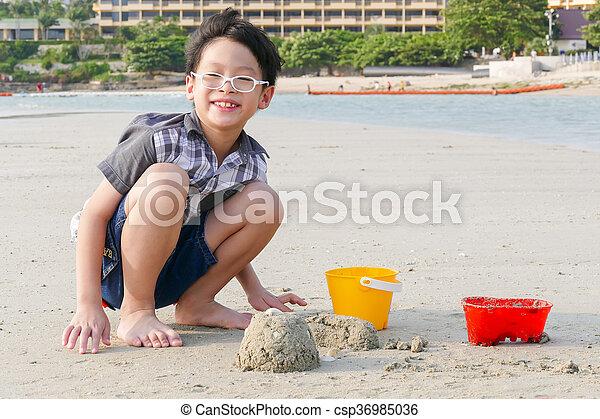 boy playing sand on beach - csp36985036
