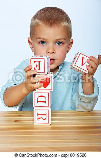 boy playing with alphabet blocks - csp10019526
