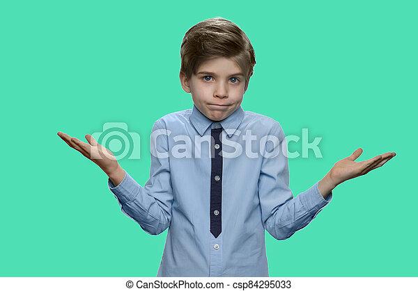 Boy shrugging shoulders against color background. - csp84295033
