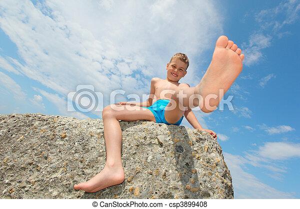 boy sits on rock, bottom view - csp3899408