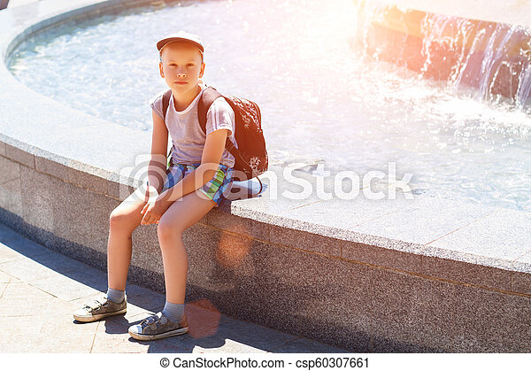 boy sitting by the fountain on a Sunny day - csp60307661
