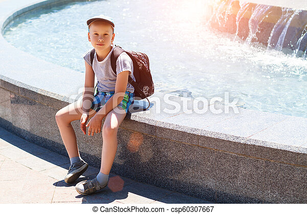 boy sitting by the fountain on a Sunny day - csp60307667