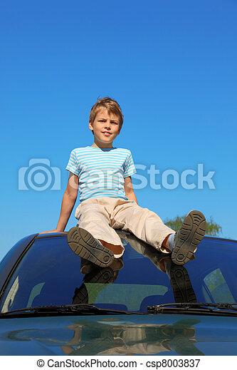 boy sitting on roof of car, blue sky - csp8003837