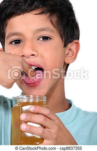 Boy tasting some honey - csp8837355