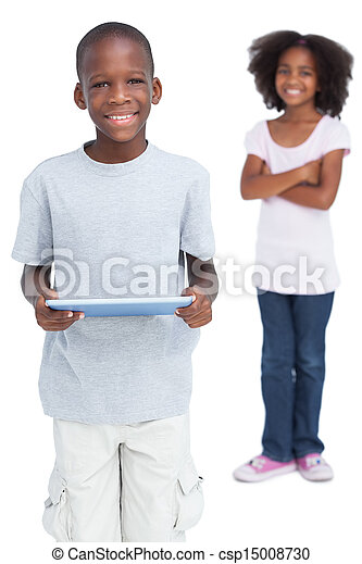 Boy using tablet pc with his sister - csp15008730