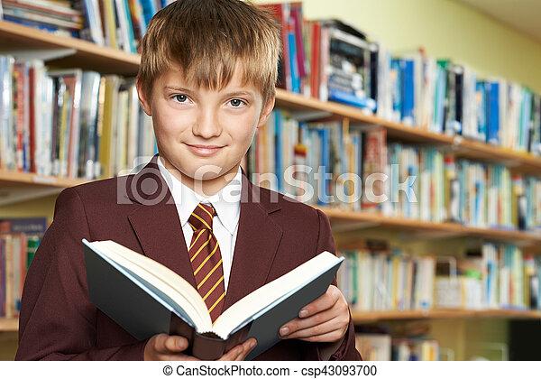 Boy Wearing School Uniform Reading Book In Library - csp43093700