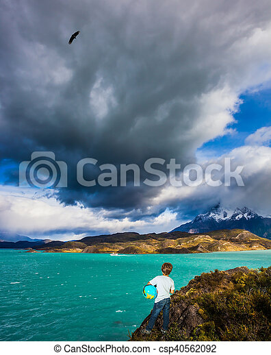Boy with a globe under his arm on lake - csp40562092