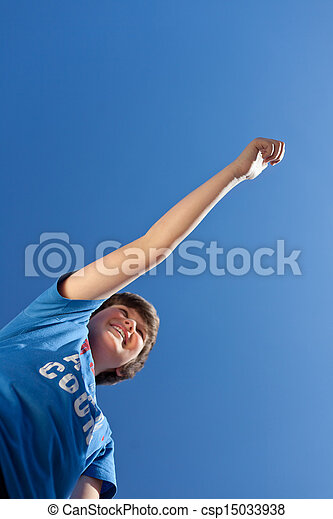 Boy With Arms Raised Celebrating Victory Against Blue Sky - csp15033938