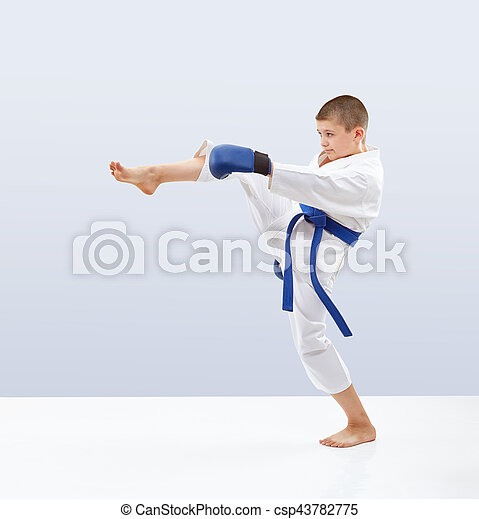Boy with blue belt and overlays on the hands is beating kicking - csp43782775