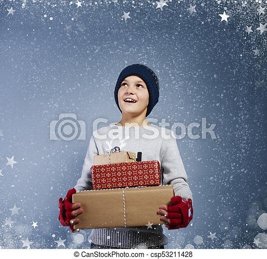 Boy with christmas present among snow falling - csp53211428