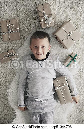 Boy with christmas present lying on back - csp51344706
