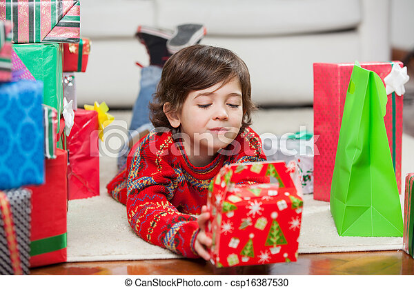 Boy With Christmas Present Lying On Floor - csp16387530