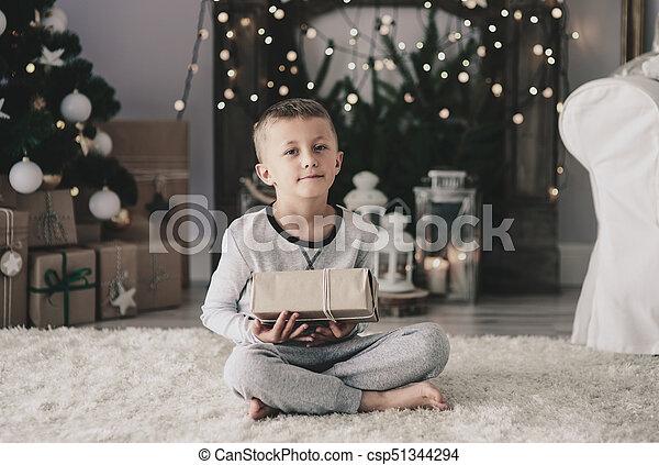 Boy with christmas present sitting on rug - csp51344294
