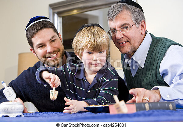 Boy with father and grandfather spinning dreidel - csp4254001
