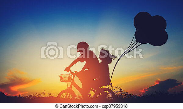 Boy with his sister riding bicycle on sunset background.Silhouette, - csp37953318