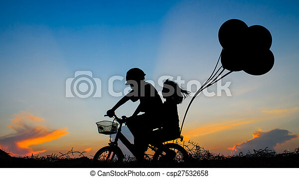Boy with his sister riding bicycle on sunset background.Silhouette, - csp27532658