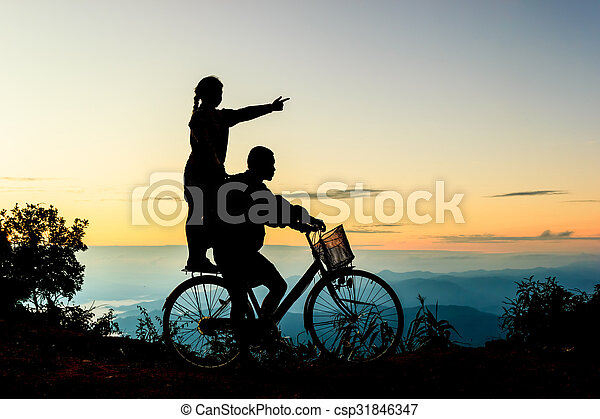 Boy with his sister riding bicycle on sunrise background.Silhouette - csp31846347