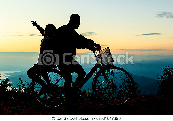 Boy with his sister riding bicycle on sunrise background.Silhouette - csp31847396