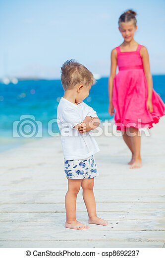 Boy with his sister walking on jetty - csp8692237