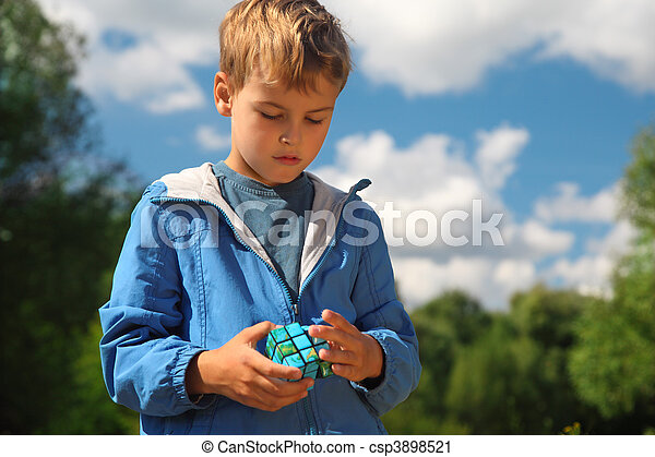 boy  with magic cube outdoor in summer - csp3898521