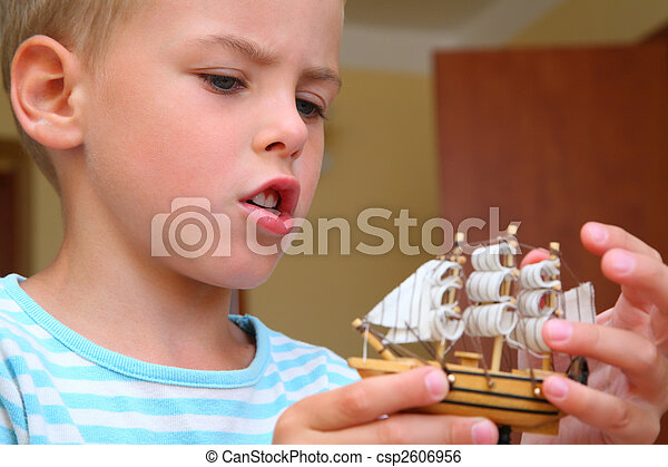 Boy with model of ship in hands - csp2606956