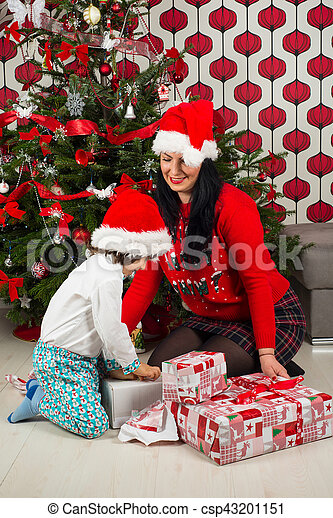 Boy with mother opening Xmas gifts - csp43201151