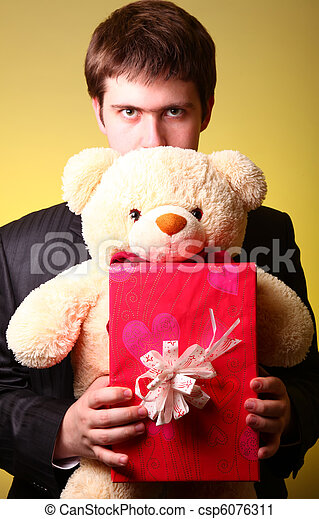 Boy with present box and teddy bear can't select a present in St. Valentine day - csp6076311