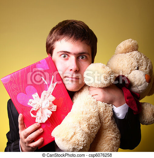 Boy with present box and teddy bear can't select a present in St. Valentine day - csp6076258