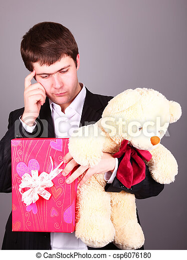 Boy with present box and teddy bear can't select a present in St. Valentine day - csp6076180