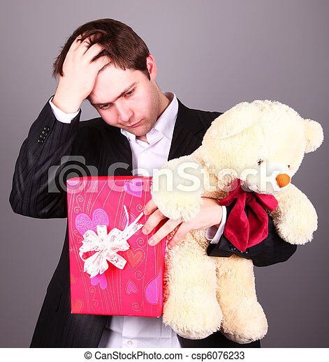 Boy with present box and teddy bear can't select a present in St. Valentine day - csp6076233