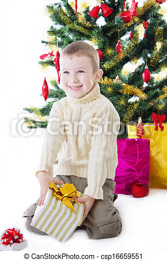 Boy with present box under Christmas tree - csp16659551