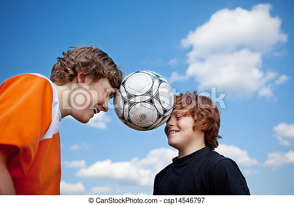 Boys Balancing Soccer Ball With Heads Against Sky - csp14546797