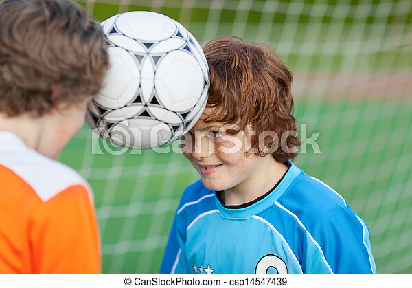 Boys Balancing Soccer Ball With Heads Against Sky - csp14547439