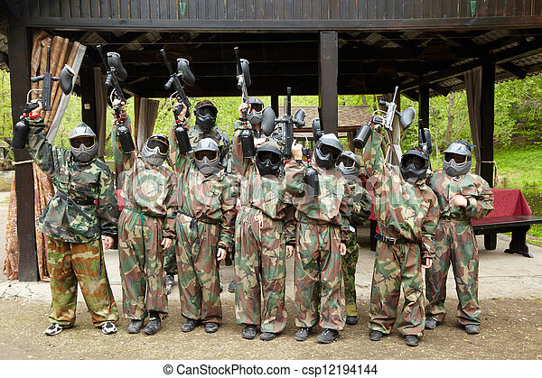 Boys dressed in camouflage stand in a row on a paintball base, raising his paintball gun up. - csp12194144