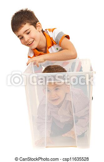 Boys having fun with a box - csp11635528